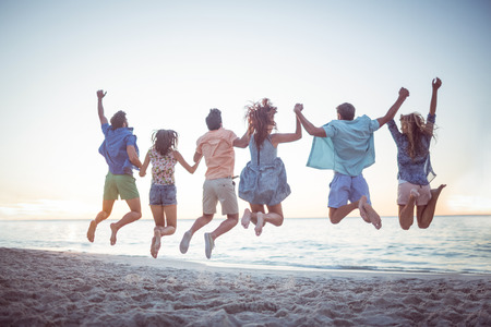 men friends: Happy friends holding hands and jumping at the beach Stock Photo