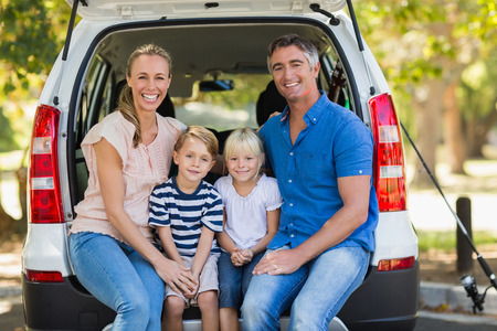 thirties portrait: Portrait of a happy family of four sitting in car trunk while on picnic Stock Photo