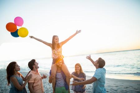 amigos: Amigos felices bailando en la arena con globos en la playa Foto de archivo