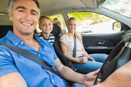 family outing: Happy family smiling at the camera in the car on a sunny day Stock Photo