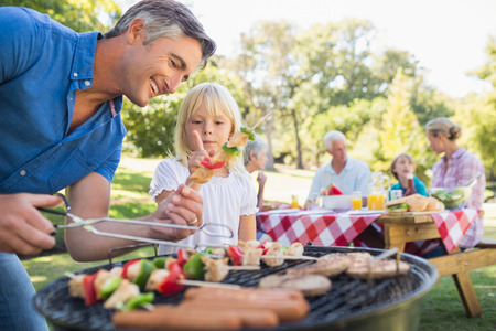 barbecue: Happy father doing barbecue with her daughter on a sunny day Stock Photo
