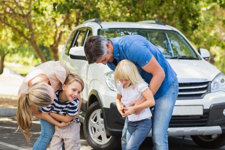 family: Familia feliz que consigue listo para viaje por carretera en un día soleado Foto de archivo