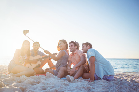 stick people: Happy hipsters taking pictures with selfie stick at the beach