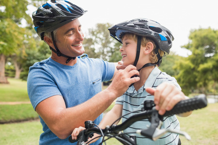 person outdoors: Happy father on a bike with his son on a sunny day