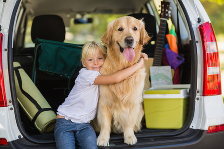 Smiling little girl with her dog in car trunk on a sunny day Stock Photo