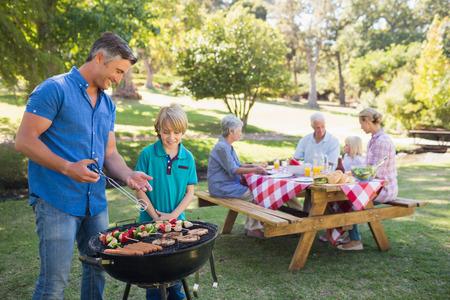 Glückliche Familie, die Picknick im Park an einem sonnigen Tag Standard-Bild