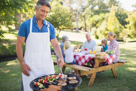 quincho: Hombre feliz haciendo barbacoa para su familia en un d�a soleado