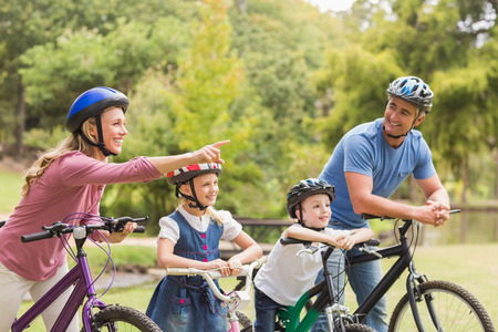 fun woman: Happy family on their bike at the park on a sunny day Stock Photo