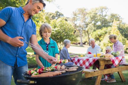 晴れた日に公園でピクニックを持つ幸せな家族