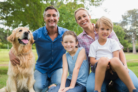 Happy family smiling at the camera with their dog on a sunny day Stock Photo
