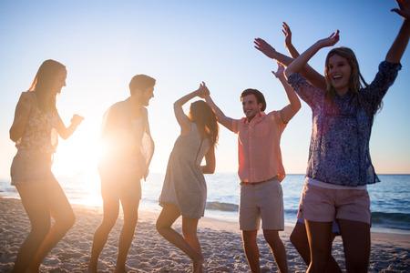 gente bailando: Amigos felices que bailan en la arena en la playa