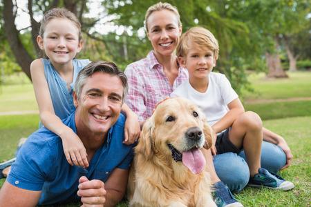 Familia feliz sonriendo a la cámara con su perro en un día soleado