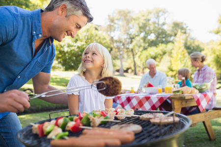 Happy father doing barbecue with her daughter on a sunny day Stock Photo