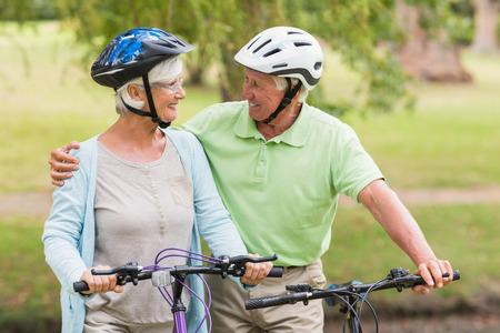 seniors: Feliz pareja senior en su bicicleta en un d�a soleado