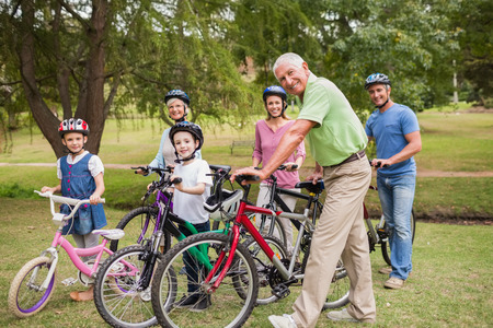 grandmother mother daughter: Happy family on their bike at the park on a sunny day Stock Photo
