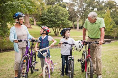 abuelos: Feliz abuelos con sus nietos en su bicicleta en un día soleado