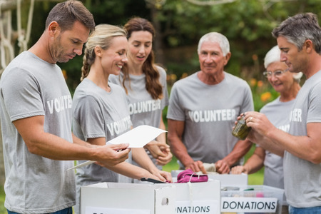 selfless: Happy volunteer looking at donation box on a sunny day Stock Photo
