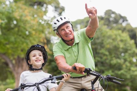 grandfather: Feliz abuelo con su nieta en su bicicleta en un d�a soleado
