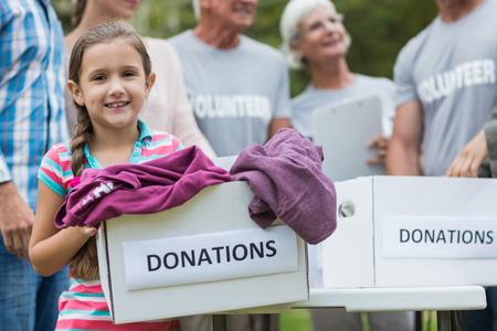 dia soleado: Familia voluntario feliz celebración de cajas de donación en un día soleado