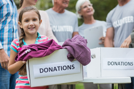 outdoor event: Happy volunteer family holding donation boxes on a sunny day
