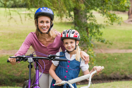 mother child: Mother and her daughter on their bike on a sunny day Stock Photo