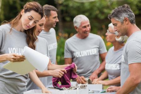 altruismo: Voluntario feliz que mira la caja de donaci�n en un d�a soleado