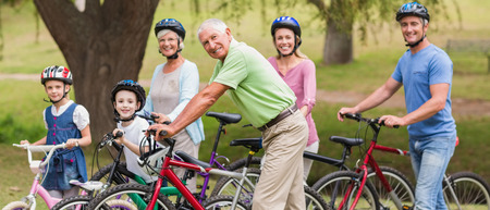 Happy family on their bike at the park on a sunny day Stock Photo