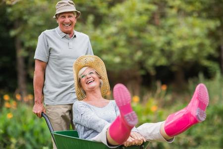 Felice coppia senior a giocare con una carriola in una giornata di sole