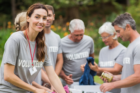 dia soleado: Voluntario feliz que mira la caja de donación en un día soleado