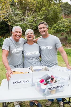 Happy family volunteer smiling at camera on a sunny day Stock Photo