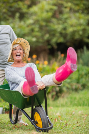 outdoor living: Happy senior couple playing with a wheelbarrow in a sunny day Stock Photo