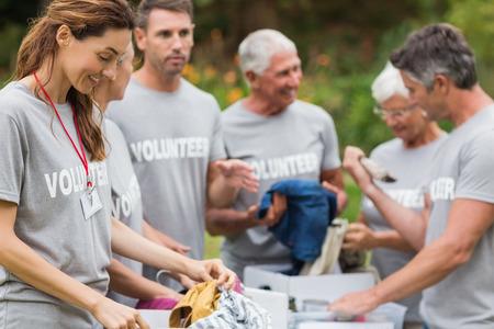 Bénévoles heureux regardant boîte de dons sur une journée ensoleillée Banque d'images