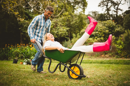 outdoor living: Happy couple playing with a wheelbarrow on a sunny day