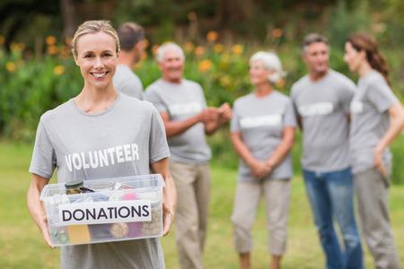 altruismo: Voluntario feliz con caja de donaci�n en un d�a soleado Foto de archivo