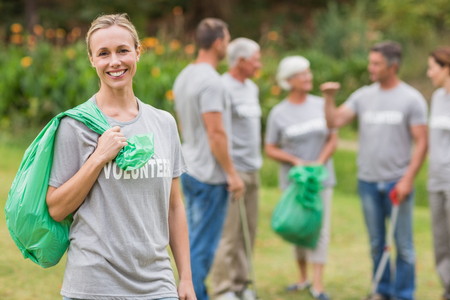 selfless: Happy volunteer collecting rubbish on a sunny day