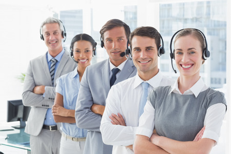 business service: Business people with headsets smiling at camera in office Stock Photo