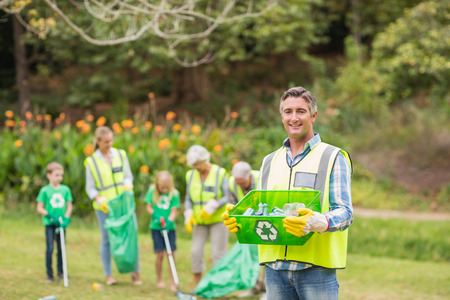 volunteer: Happy family collecting rubbish on a sunny day