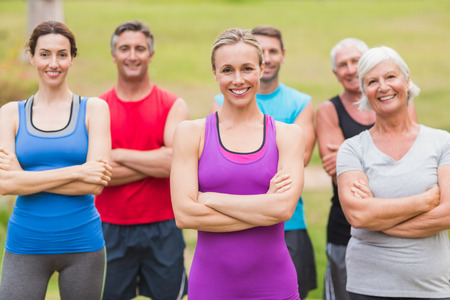 Happy athletic group smiling at camera with hands crossed on a sunny day Stock Photo