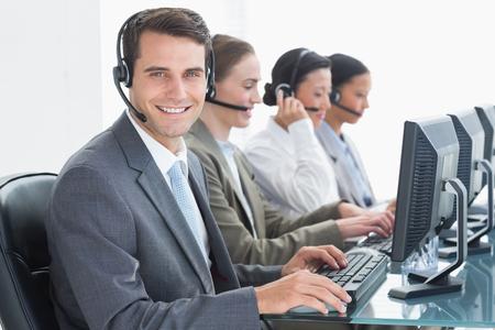 servicio al cliente: Hombres de negocios con los auriculares que usan ordenadores en la oficina