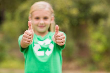 altruism: Niña feliz en verde con los pulgares para arriba en un día soleado Foto de archivo