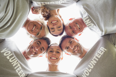 volunteer: Happy volunteer family looking down at the camera on a sunny day Stock Photo