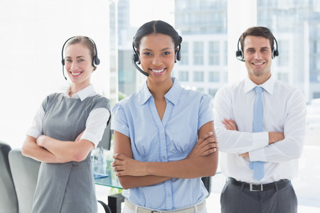 headset woman: Business people with headsets smiling at camera in office Stock Photo