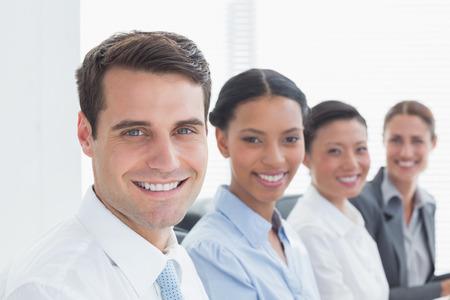 personas mirando: Hombres de negocios sonrientes mirando la c�mara en la oficina Foto de archivo
