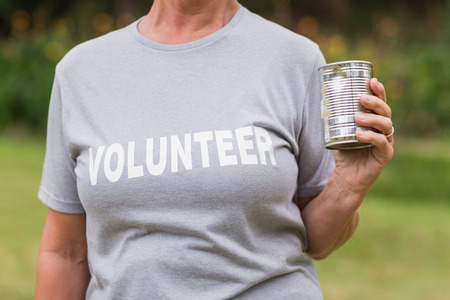 tin can: Volunteer holding tin can on a sunny day