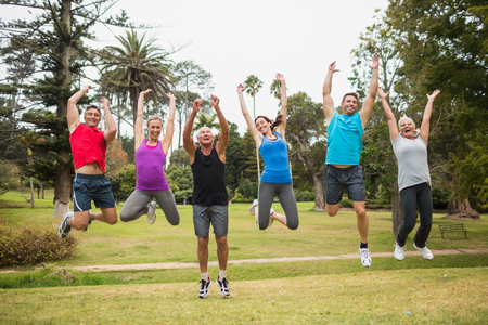 senior exercise: Happy athletic jumping together on a sunny day Stock Photo