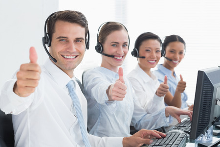 42210026: Business people looking at camera with thumbs up in office