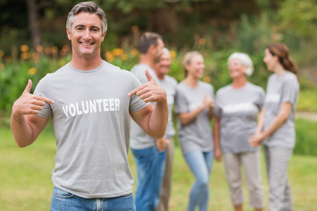 community: Happy volunteer showing his t-shirt to camera on a sunny day Stock Photo
