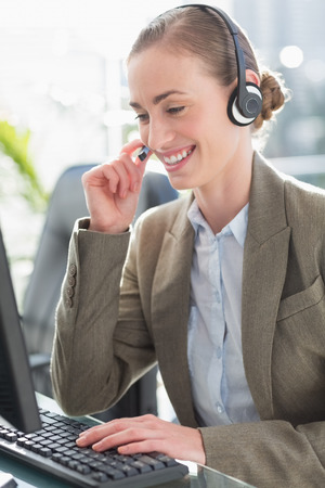 tech support: Smiling businesswoman with headset using computers in office