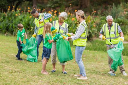 altruismo: Familia feliz recogida de basura en un d�a soleado