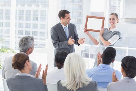 Business people receiving award in meeting room